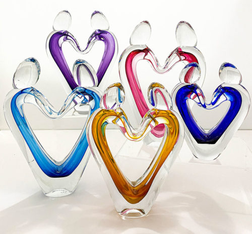 five glass heart sculptures in various colors