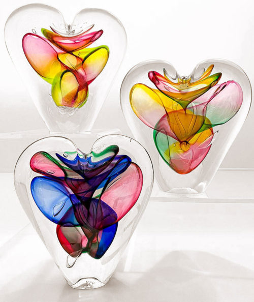 three colorful crystal heart sculptures